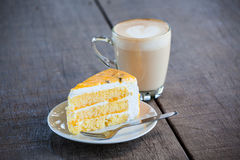 Cake with cup of coffee on old wood table. Yellow cake with cup of latte coffee on old wood table, light nature Royalty Free Stock Photography