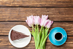 Cake and cup of coffee with tulips Stock Photo