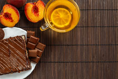 Cake with a cup of tea on a dark wooden background.Dessert of cottage cheese in chocolate glaze Royalty Free Stock Images