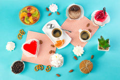 Cake, cups with coffee, cookies on a bright background. Morning breakfast Stock Photos