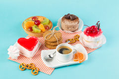 Cake, cups with coffee, cookies on a bright background. Morning breakfast Stock Images