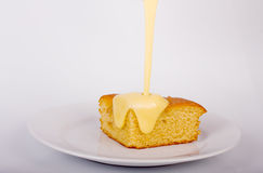 Cake and custard. Cake with poured Custard on a plate royalty free stock images