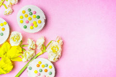 Cake and daffodils flowers on pink background, top view, place for text Royalty Free Stock Photos