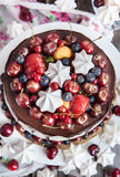 Cake decorated with chocolate, meringues and fresh berries Stock Image