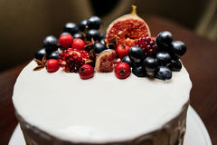 Cake decorated with fresh fruits on the white plate. On a wooden table. Wedding cake Royalty Free Stock Images