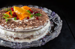 Cake decoreted by oranges, cranberries and green leaves Royalty Free Stock Photos