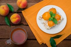 Cake with diced peach, whipped cream and mint. Wooden rustic background. Top view Royalty Free Stock Photography