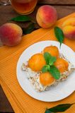 Cake with diced peach, whipped cream and mint. Wooden rustic background. Top view Stock Image