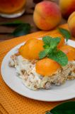 Cake with diced peach, whipped cream and mint. Wooden rustic background. Top view Stock Photos