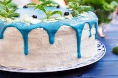 Cake die met blauwe room, munt en bosbessen wordt verfraaid Stock Fotografie