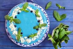 Cake die met blauwe room, munt en bosbessen wordt verfraaid Stock Afbeeldingen