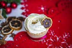 Cake, die zich op een rood Kerstmisservet bevinden op een witte houten die lijst door een groene slinger en Kerstmislichten wordt Royalty-vrije Stock Foto's