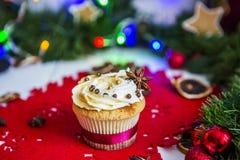 Cake, die zich op een rood Kerstmisservet bevinden op een witte houten die lijst door een groene slinger en Kerstmislichten wordt Royalty-vrije Stock Fotografie