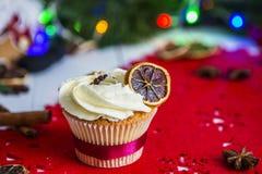 Cake, die zich op een rood Kerstmisservet bevinden op een witte houten die lijst door een groene slinger en Kerstmislichten wordt Royalty-vrije Stock Foto