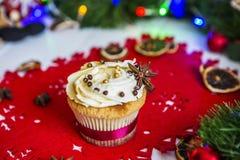 Cake, die zich op een rood Kerstmisservet bevinden op een witte houten die lijst door een groene slinger en Kerstmislichten wordt Royalty-vrije Stock Afbeelding