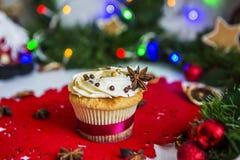 Cake, die zich op een rood Kerstmisservet bevinden op een witte houten die lijst door een groene slinger en Kerstmislichten wordt Stock Fotografie