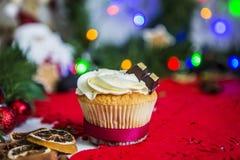 Cake, die zich op een rood Kerstmisservet bevinden op een witte houten die lijst door een groene slinger en Kerstmislichten wordt Stock Afbeelding