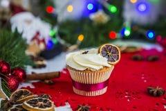 Cake, die zich op een rood Kerstmisservet bevinden op een witte houten die lijst door een groene slinger en Kerstmislichten wordt Stock Foto's