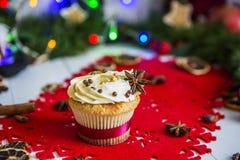 Cake, die zich op een rood Kerstmisservet bevinden op een witte houten die lijst door een groene slinger en Kerstmislichten wordt Stock Afbeeldingen