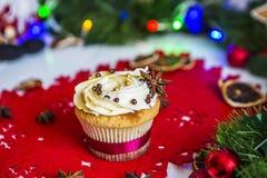 Cake, die zich op een rood Kerstmisservet bevinden op een witte houten die lijst door een groene slinger en Kerstmislichten wordt Royalty-vrije Stock Afbeeldingen