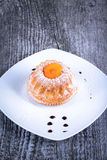 Cake with dry apricot and sugar powder on the white plate on wooden Royalty Free Stock Photo