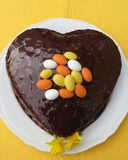Cake for Easter time with decoration of chocolate eggs and Daffodils. Cake in heart form and covered with ganache and decorated with candy eggs and Daffodils Stock Photography