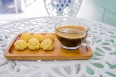 Cake eclair or Cream Puffs or Profiterole with coffee cup in wood plate on the white table. Cake eclair or Cream Puffs or Profiterole with coffee cup in wood Royalty Free Stock Images