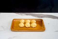 Cake eclair or Cream Puffs or Profiterole in wood plate on the white table. Cake eclair or Cream Puffs or Profiterole in wood plate on the white table Stock Photos