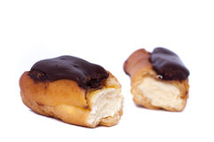 Cake eclair custard is broken in half on white. Delicious Cake eclair custard is broken in half on white royalty free stock photography