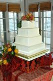 Cake for a Fall Wedding. Fall decorations adorn this wedding cake at a reception.  Solid white cake with four tiers.  Sits on a Burgundy sheer cloth Stock Photos