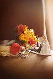 Cake figurines with bouquet on chair Stock Photos