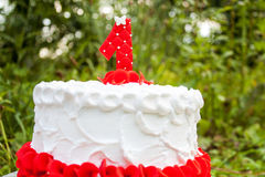 Cake for the first birthday. Red and white cake for the first birthday on the grass Royalty Free Stock Photography