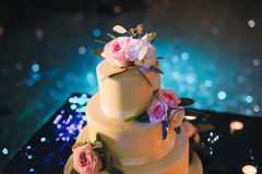 Cake with flowers. Cake decorated with flowers on a blue background with bokeh Royalty Free Stock Photos