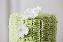 Cake with Fondant Ruffles and Sugar Flowers. Profile Close Up of Exquisite Cake Decorated with Green Fondant Ruffles and White Sugar Flowers Stock Image