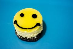 Cake in the form of an emoticon. On a blue background Royalty Free Stock Image