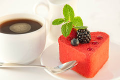 Cake in the form of heart. With a blackberry, a raspberry and mint, a cup of coffee stock photos