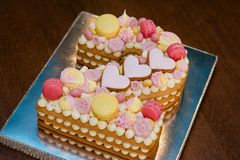 A cake in the form of two figures. Number two Biscuit cake. Birthday cake with pink hearts, macaroni and bezye. Cake for a girl stock images