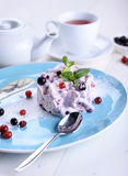 Cake with fresh berries on a blue plate next to a cup of tea. And a teapot. Berry cake with tea Stock Photos