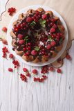 Cake with fresh berries and chocolate glaze. top view vertical. Cake with fresh berries and chocolate glaze on a plate. vertical top view royalty free stock photography