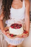 Cake with fresh berries and white glaze. In a woman's hands Stock Images