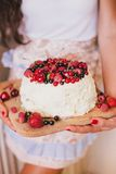 Cake with fresh berries and white glaze. In a woman's hands Royalty Free Stock Images