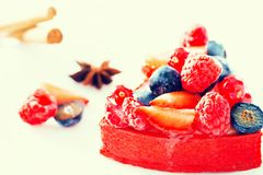Cake with fresh forest berries with cinnamon and anise. Delicious cake with fresh forest berries with cinnamon and anise royalty free stock image