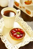 Cake with fresh strawberries and tea Stock Images
