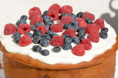 Cake with frosting covered in raspberries and blueberries Royalty Free Stock Image