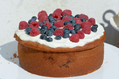 Cake with frosting covered in raspberries and blueberries Stock Photo