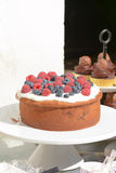 Cake with frosting covered in raspberries and blueberries Stock Photography