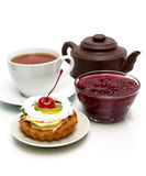 Cake with fruit, cranberry jam, a cup of tea and a clay pot on a Royalty Free Stock Images