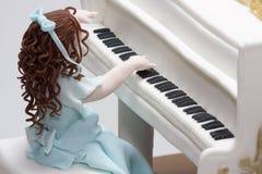 Cake girl playing grand piano Stock Image