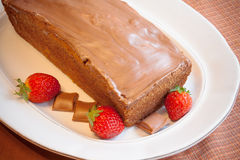 Cake with glaze of chocolate and strawberries  in the white dish Stock Image