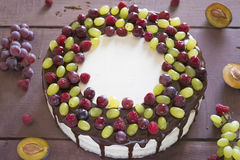 Cake with grapes. Raspberry and chocolate on the wooden table Stock Images